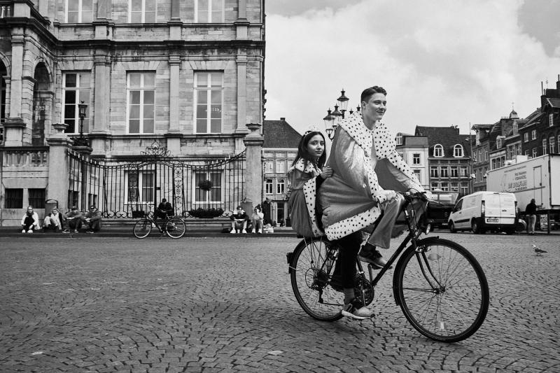 jong stel in koningsmantel op de fiets