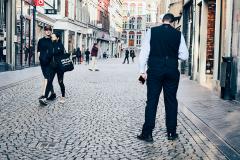 beveiliger op bijna lege winkelstraat tijdens corona pandemie